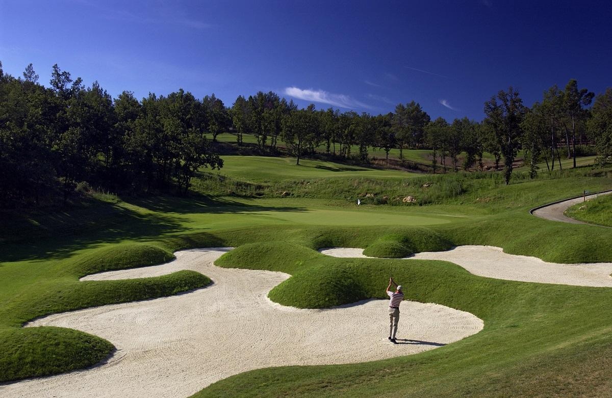 Golfer plays a bunker shot at Le Riou course Domaine de Terre Blanche